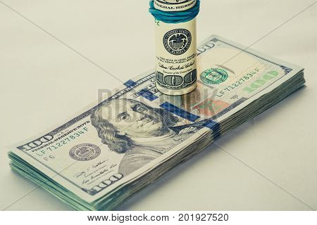 A coiled 100 dollar bill which rests on another angled 100 dollar bill isolated on white background. American bank notes isolated on the white background