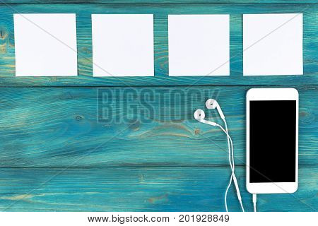 Overhead view of mobile phone with isolated screen and in-ear headphones and white empty blank sheets on black wooden table floor. Empty space for text copy space empty blank screen