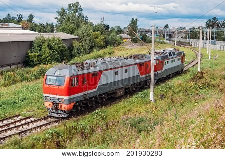 Attached To Each Other Electric Locomotive And Diesel Locomotive At The Turn Of The Iron Dog