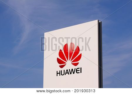 Huawei logotype on white panel sign by headquarters with clear blue sky. Chinese multinational company, is the largest telecommunications equipment maker in the world: Copenhagen, August 29, 2017