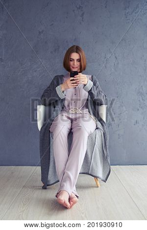 Vertical of relaxed woman using smartphone and sitting on armchair with copy space