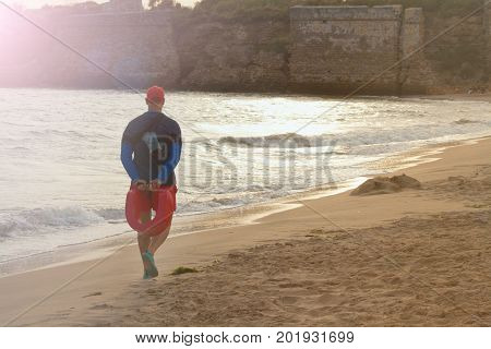 the lifeguard walks along the beach  v