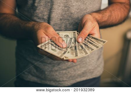 A man in a gray T-shirt holds dollars in his hands. Bank. Casino. Salary. Rates.