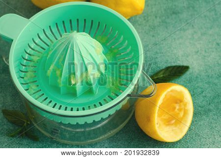 Fresh lemons and mint with citrus squeezer on turquoise background. Horizontal, top view, toned