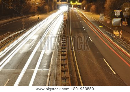 Car lights on a german highway construction site with signs at night, long exposure photo of traffic