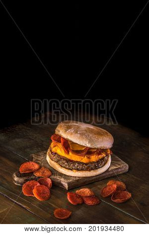 Delicious hamburger with fried peperoni, melted cheddar and barbecue sauce on a dark wood background