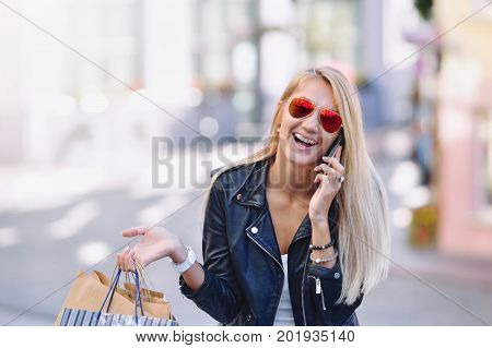Young Smiling Woman With Shopping Bags Talk By Cellular Telephone.