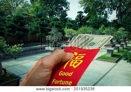Chinese Bonsai garden and a red envelope in hong bao.Is traditional to give money during the Chinese New Year in China.Envelope with the chinese words meaning Good fortune on it, and Dollar bills