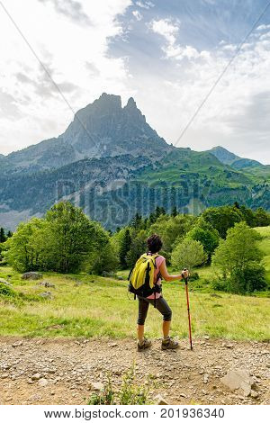 a woman hiker with Pic du Midi d'Ossau in the French Pyrenees