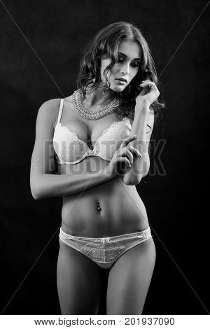 beautiful woman in white lingerie on black background, monochrome