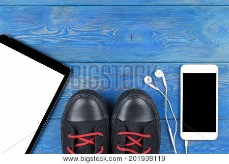 Top view of sports shoes by tablet computer and mobile phone with isolated screen and in-ear headphones and white empty blank sheets on black wooden table floor. Empty space for text copy space empty blank screen