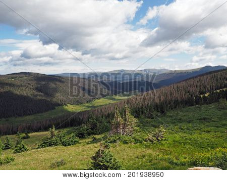 Summer in the Rocky Mountains National Park in Colorado. White puffy clouds in a blue sky cast shadows over the moutains and meadows below