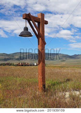 Rustic style wood street light on a prairie in Colorado. There is a bright blue sky overhead with white puffy clouds. In the background are mountains.