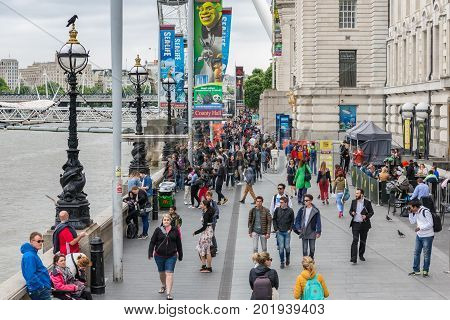 LONDON ENGLAND - JUNE 08 2017: People at promenade between London Eye and Westminster Bridge at south bank of London England