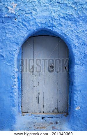 Detail of a wood door painted in blue in the beautiful town of Chefchaouen in Morocco North Africa
