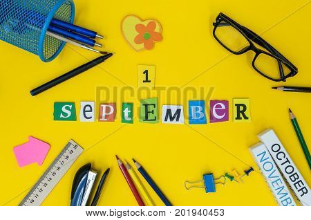 September 1st. Day 1 of month, Back to school concept. Calendar on teacher or student workplace background with school supplies on yellow table. Autumn time.