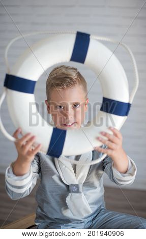 Cute sailor boy holding a life preserver in studio