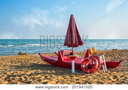 Lifeguard tools umbrellalifebuoy and rescue boat against beachsea and sky