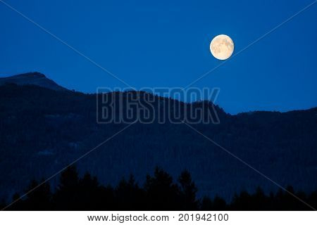 Full moon in dusk over dark mountains with blue sky in background and forest in foreground