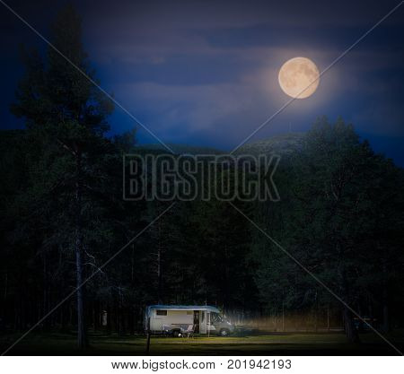 Recreational vehicle at night in Norway Europe. Hills and dark cloudy sky with full moon. Travel by RV. Nordic country Europe Scandinavia.