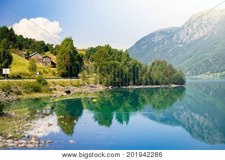 Norway country houses. Lake and mountains. Blue cloudy sky. Nordic Scandinavia Europe travel