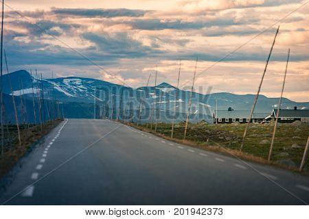 Empty country road in Norway Europe Scandinavia. Auto travel on sunset. Orange sky with clouds.