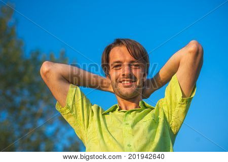 A color portrait photo of a happy smiling brunette haired man wearing a yellow lime green shirt against a blue sky backround.