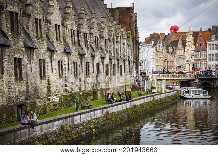 GHENT BELGIUM - JUNE 22 2016: Horizontal picture of one of Ghent's canal with a boat houses sidewalk with benches with people in cloudy day in Ghent.