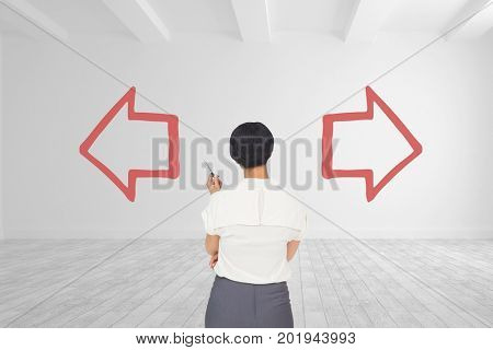 Digital composite of Business woman standing against white room background with red arrows