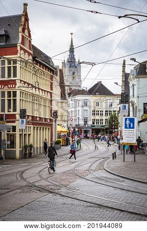 GHENT BELGIUM - JUNE 22 2016: Vertical picture of the downtown in Ghent in a cloudy day with curved tram rails houses stores people and a church in the background.