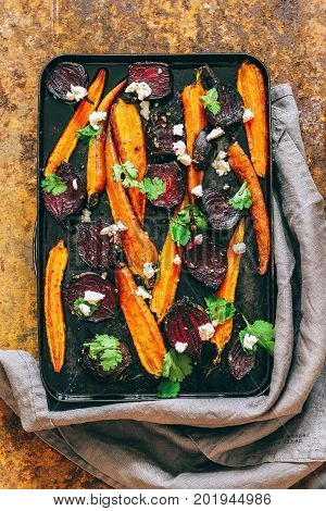 Baked beets and carrots in a vintage black pan with ricotta fennel seeds and fresh coriander leaves on a rusty background autumn dish. Top view.