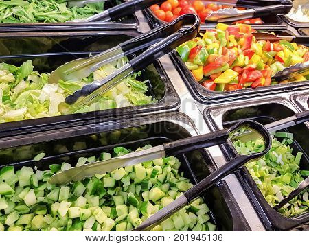 Concept of self-service bar or restaurant with a choice of different types of fruit and vegetable salads