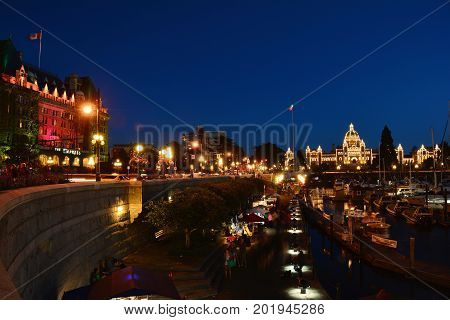 Victoria BC,Canada,August 9th 2014.Victoria's busy inner harbor at nighttime with the iconic Empress hotel parliament buildings,boats and many tourists enjoying Victoria's beauty.