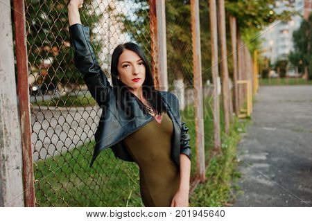 Fabulous Woman In Dress And Leather Jacket Standing Next To The Net.