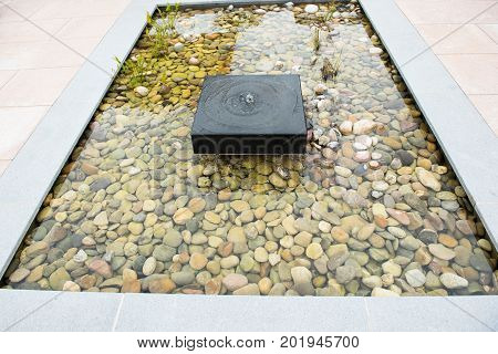 Relaxing zen fountain with pebbles and grass