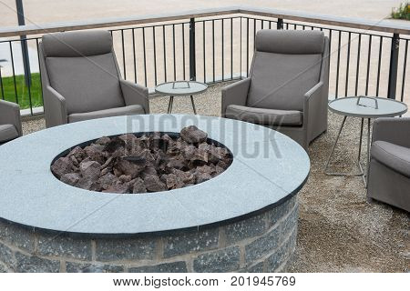 Round gas fire station with basalt stones with tables and lounges