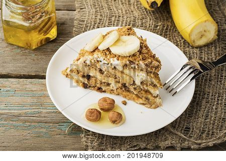 Fresh homemade banana puff cake with biscuit, sour cream, banana slices, honey on a plain gray wooden background in horizontal design. A bunch of bananas in the background