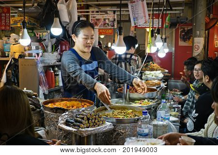 Seoul, South Korea - April 08, 2017: Woman Vendor Serving Customers At Gwangjang Market In Seoul. It