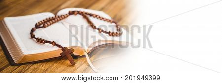 Digital composite of Rosary on bible and white transition