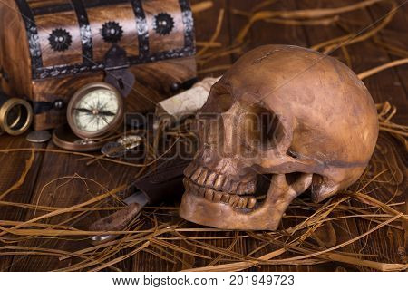 Human skull and knife with treasure chest and compass in background