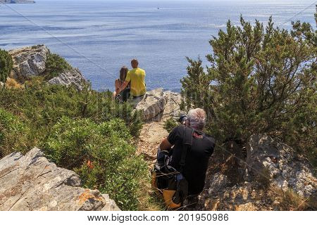 DUGI OTOK, CROATIA - SEPTEMBER 7, 2016: Unidentified photographer takes pictures of a couple that sits on steep coastal cliffs of the island in Telascica Nature Park.