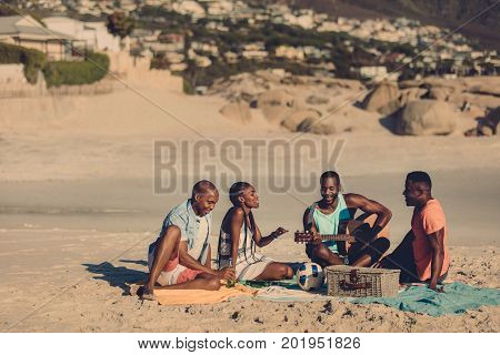 Group of friends with guitar sitting on beach. African people enjoying at the seaside picnic.