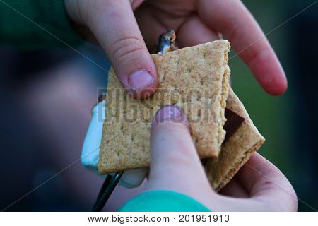 Hands Pulling A Marshmallow Off A Skewer To Make A Smore