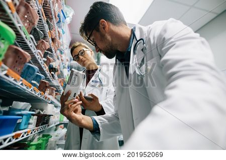 Two doctors in hospital pharmacy looking for prescribed medicine. Medical staff stocking at drugstore.