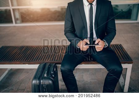 Cropped shot of young businessman sitting on bench with suitcase and using digital tablet. Man waiting in public transport station.