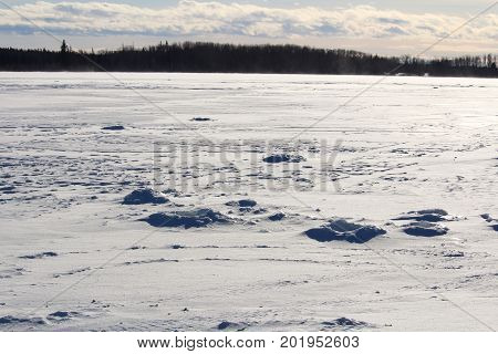 Old Ice Fishing Holes On A Windy Lake