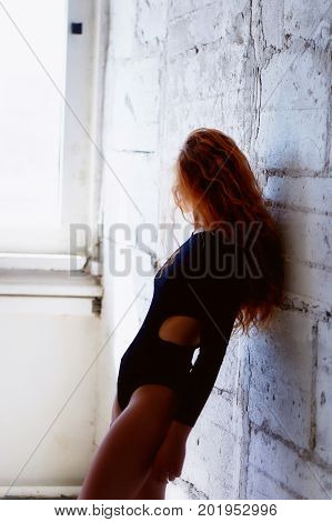 Model tests. Beautiful redhead girl with curly hair. Natural color. Demonstrates the flexibility for yoga, aerobics and ballet on the bright background of brick wall. Studio-loft. Dressed in a black bodysuit.