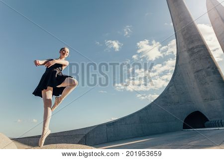 Ballet dancer practicing dance moves outdoors with blue sky and monument in the background. Female dancer balancing on one toe in pointe shoes on a rock.