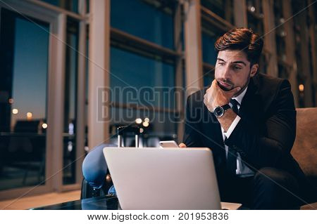 Young businessman waiting at airport lounge and looking at laptop. Caucasian male business executive sitting in waiting room at airport terminal.