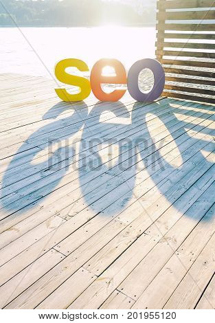 The Word Seo By Large Colored Letters Creating A Shadow On The Wooden Terrace On The River Bank. Sun